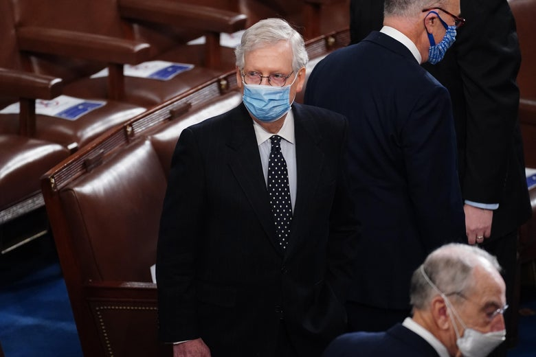 McConnell, wearing a medical mask, stands among other senators.