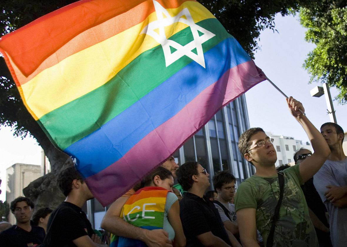 An Israeli man waves a rainbow flag bearing the Star of David