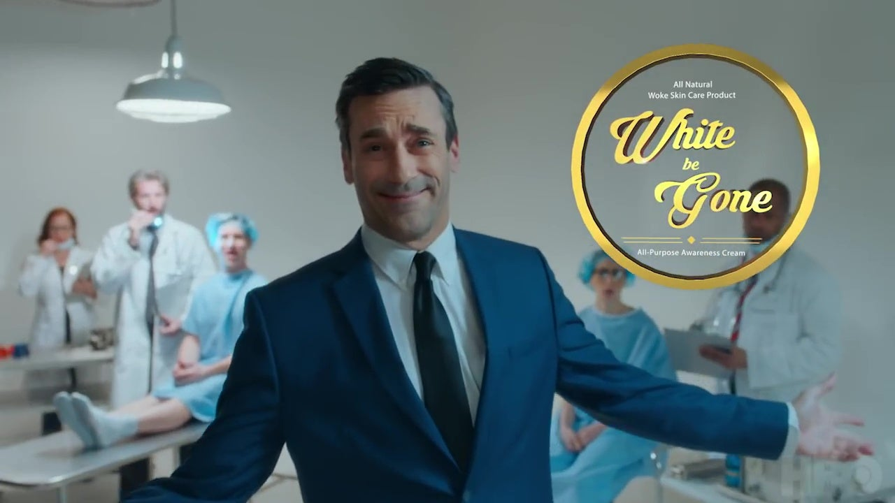 "Jon Hamm, smiling in an insincere-pitchman sort of way, in front of a logo for ""White Be Gone."""