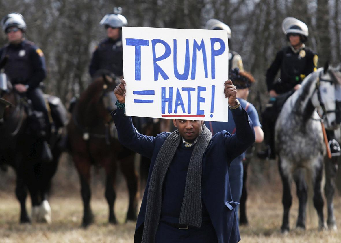 An anti-Trump protester holds his protest sign in front of mounted police outside a rally for Republican U.S. presidential candidate Donald Trump in Cleveland, Ohio, U.S. March 12, 2016.