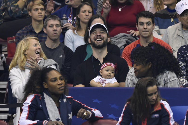 Serena Williams and her husband and child watch a tennis match.