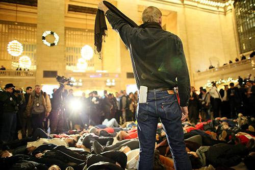 A man symbolically chokes himself with a scarf during a protest in Grand Central Terminal December 3, 2014 in New York.