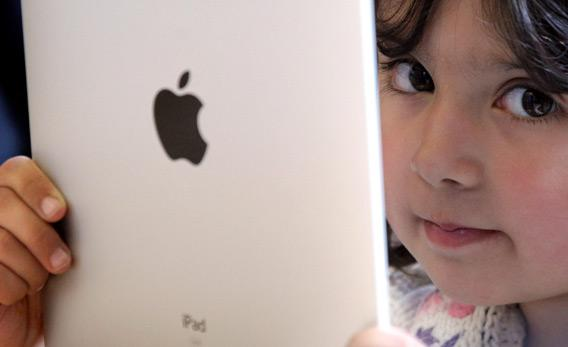 A young girl playing with an iPad.