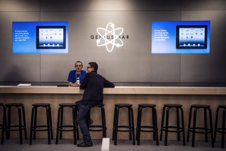 A man sits at an Apple Genius Bar.