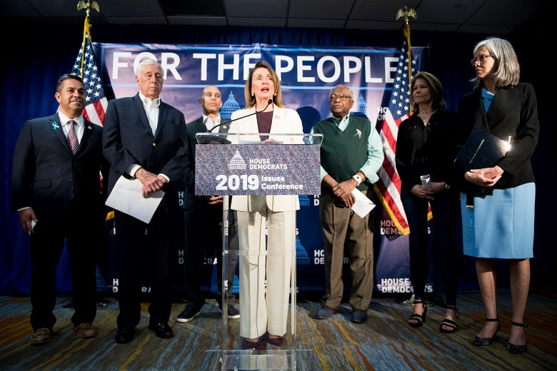 Speaker of the House Nancy Pelosi speaking at a podium, flanked from left by Assistant Democratic Leader Ben Ray Luján, House Majority Leader Steny Hoyer, Democratic Caucus Chair Hakeem Jeffries, House Majority Whip Jim Clyburn, Democratic Congressional Campaign Committee Chair Cheri Bustos, and Democratic Caucus Vice Chair Katherine Clark.