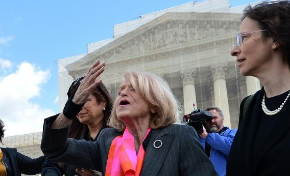 Demonstrators stand outside the Supreme Court in Washington, Tuesday, March 26, 2013, where the court will hear arguments on California's voter approved ban on same-sex marriage, Proposition 8.