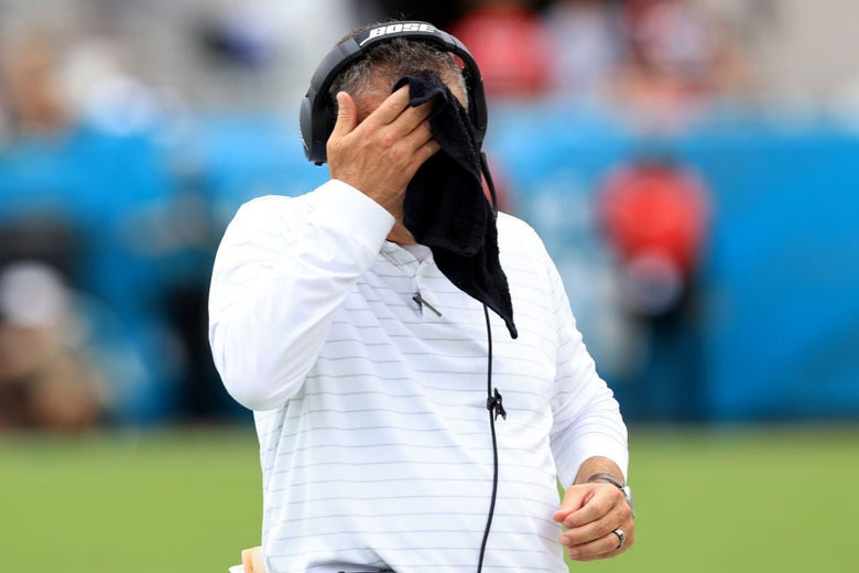 Meyer, wearing a headset and a white shirt, wipes his face with a black cloth.