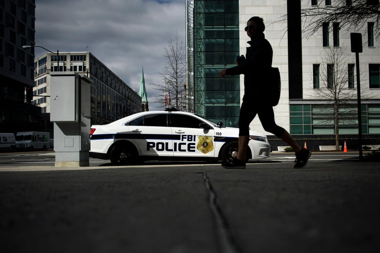 A woman walks past an FBI police car.