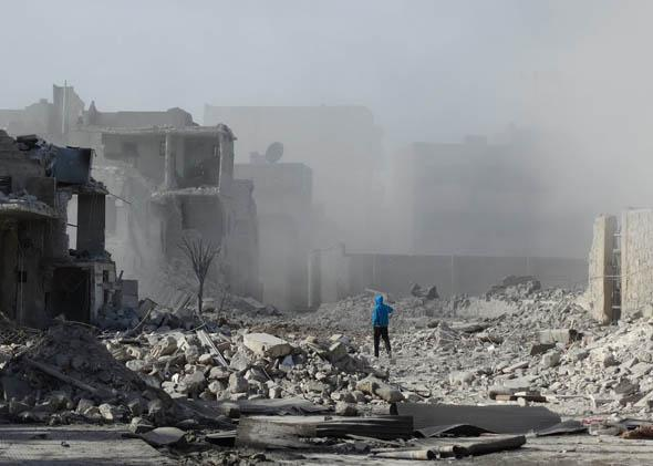A Syrian man walks amid debris and dust following an alleged air strike by Syrian government forces on January 31, 2014 in the northern Syrian city of Aleppo.