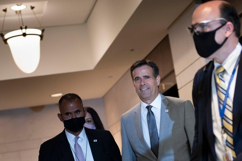 Ratcliffe, maskless and smiling, stands between two men wearing masks in a hallway