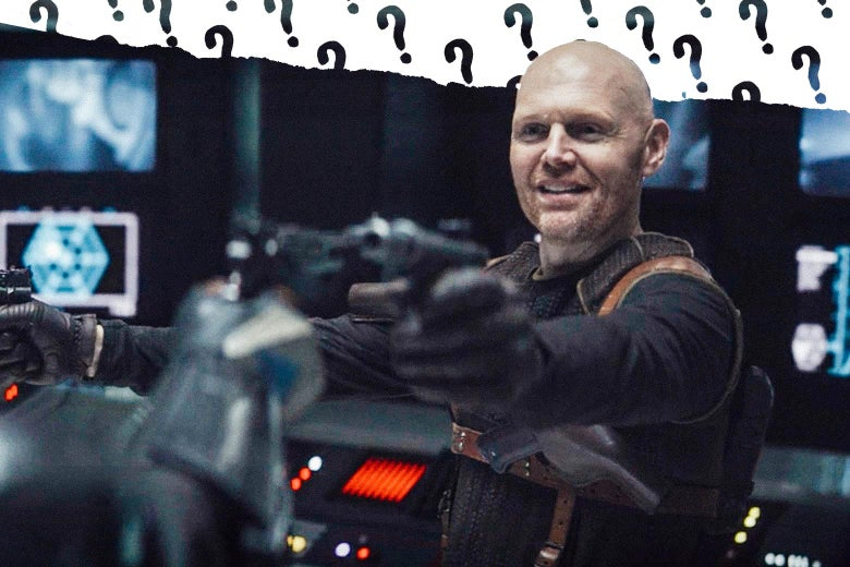 Bill Burr as Migs Mayfeld holds a blaster.