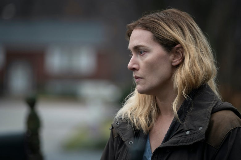 Side profile of Kate Winslet as Mare looking pensive, standing outside in a jacket