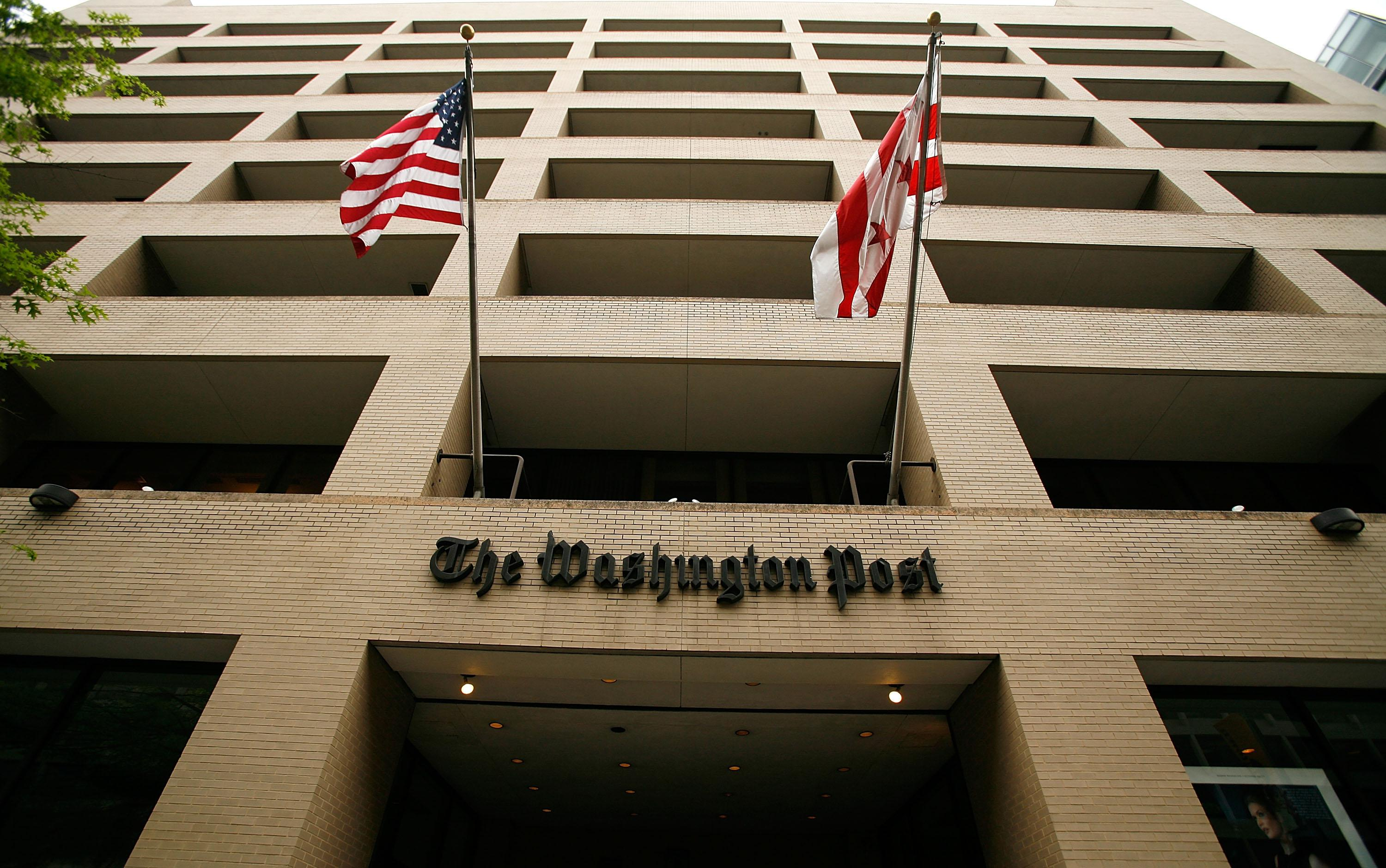 Flags wave in front of the Washington Post building on May 1, 2009, in Washington, D.C. The newspaper has announced its first-quarter earnings with a net loss of $19.5 million.