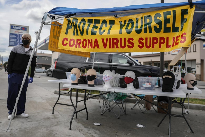 "In a parking lot, a stand selling coronavirus supplies including face masks, with a sign that says ""Protect Yourself"""