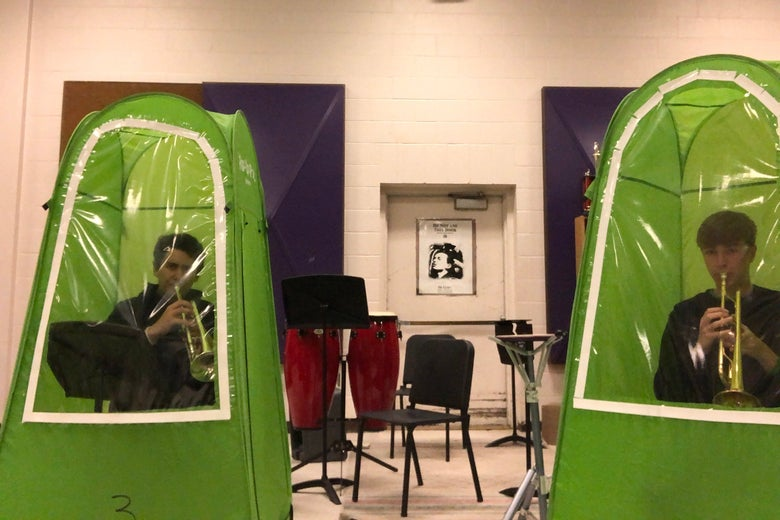 Two trumpet players practice in separate green tents inside a school band room.