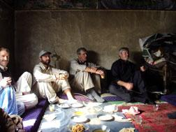Tom Grams, Glen Lapp, Tom Little, and Dan Terry, talking in a Nuristani home. Click image to expand.