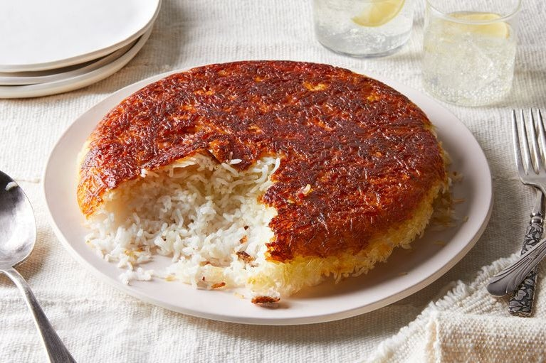 On a plate, a round cake of rice that is white and loose on the bottom and brown and packed on top.