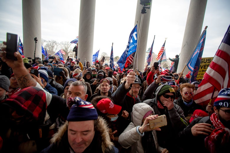 Trump supporters swarm between the Capitol columns carrying Trump flags and American flags