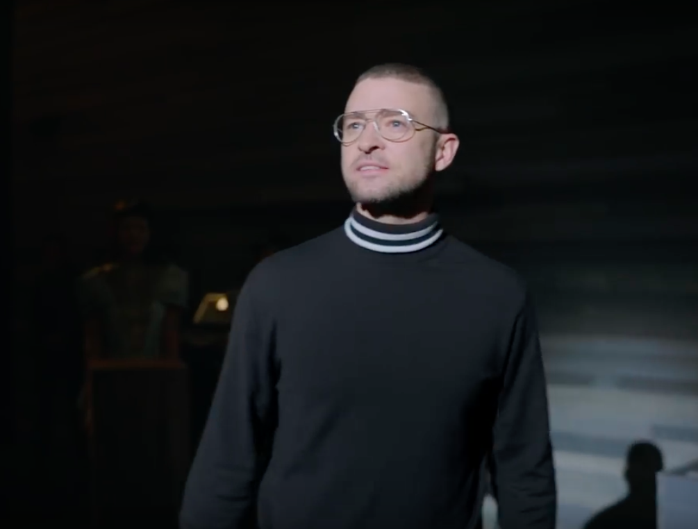 Justin Timberlake wears a black turtleneck and glasses on a stage