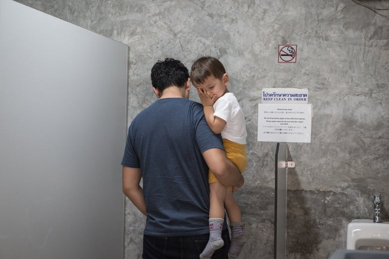 Rocco being held by his father while in a public bathroom.