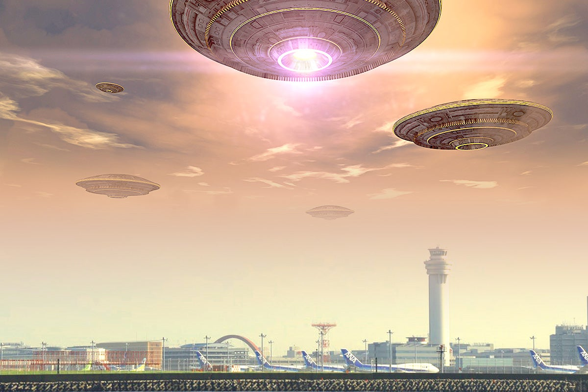 Photo illustration: A bunch of flying saucer-looking objects floating above an airport.