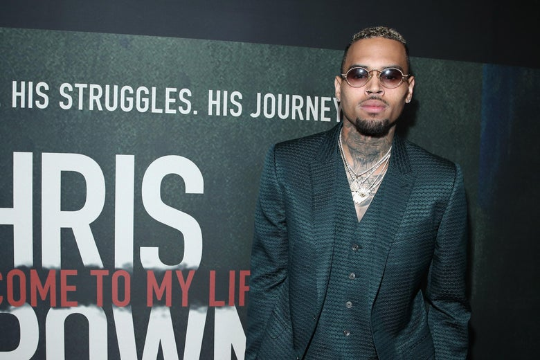 """Chris Brown stands in front of a backdrop that says, """"His struggles. His journey. Chris Brown. Welcome to my life."""""""