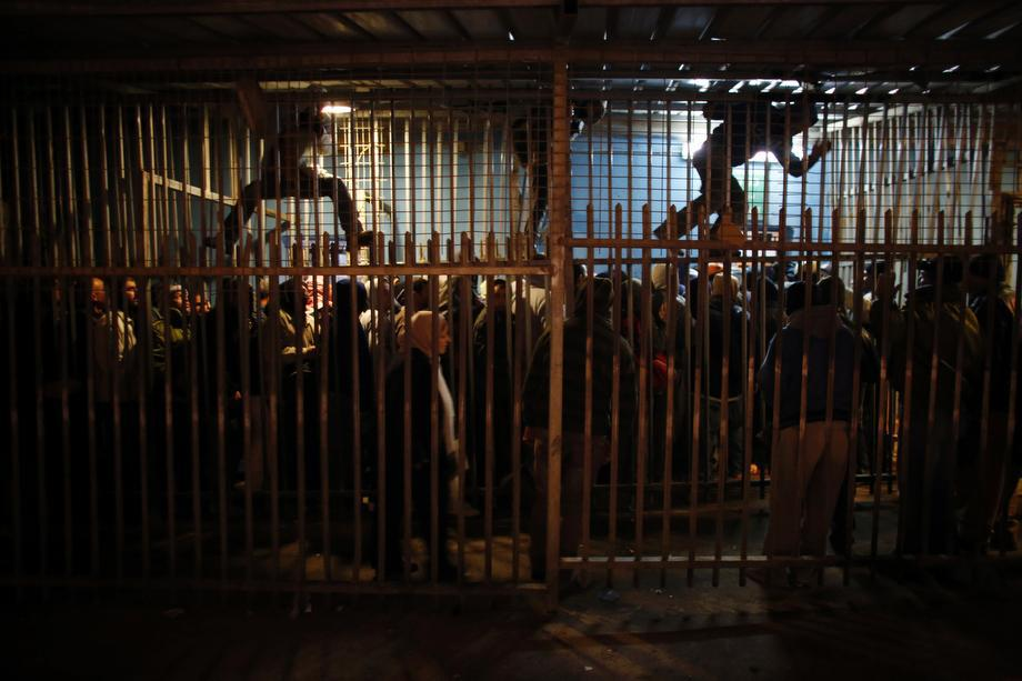 Palestinian labourers wait to cross into Jerusalem at an Israeli checkpoint in the West Bank town of Bethlehem on March 18, 2013.