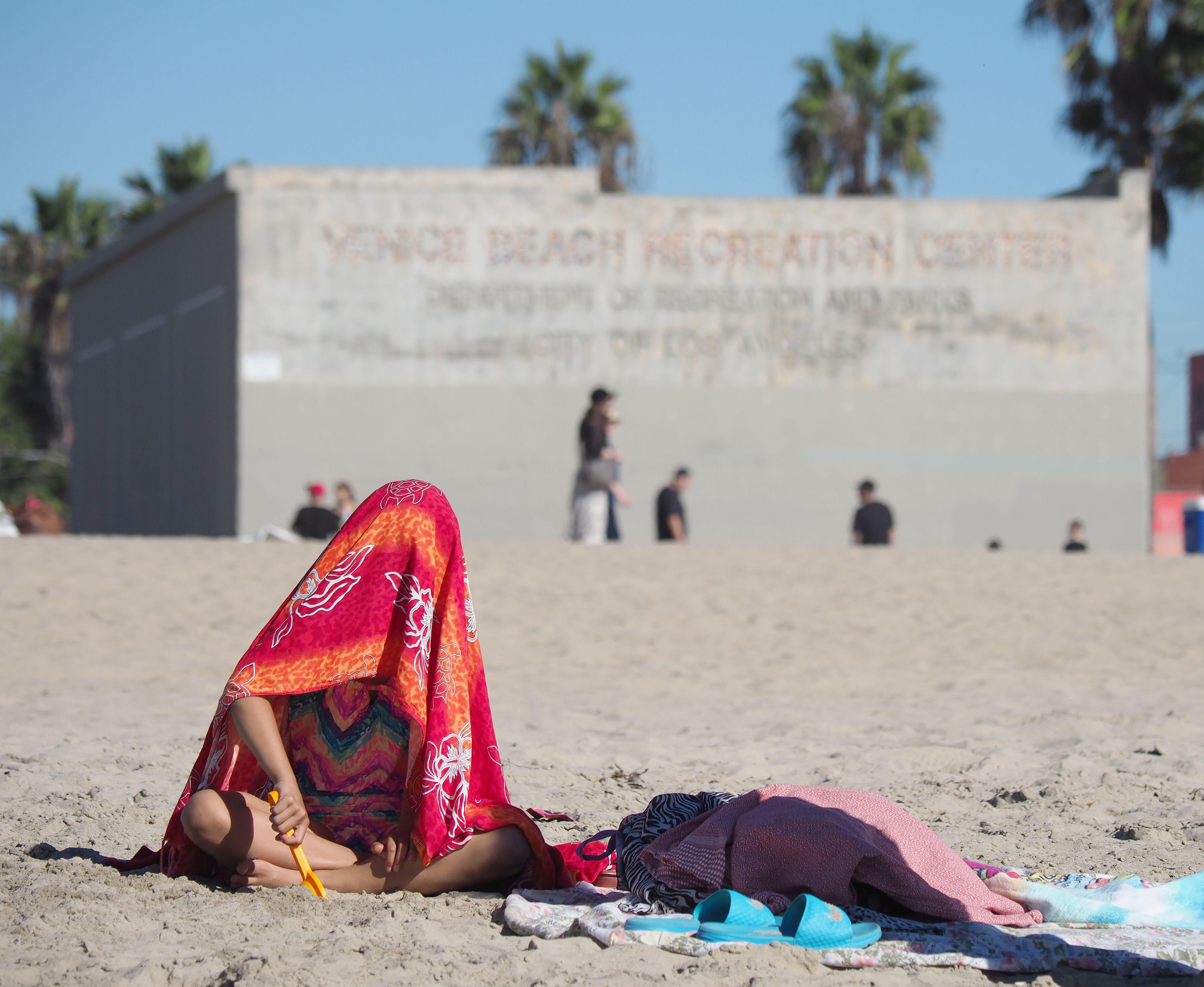A young beach goer covers her head with a towel to stave off the heat.