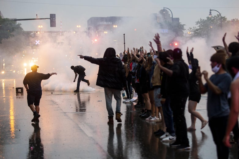 Protesters stand in a line in the street with their hands up as tear gas floods the scene.
