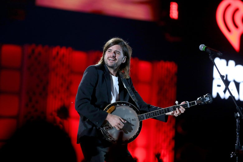 A man with long hair plays a banjo while wearing a black blazer and white T-shirt. He is on stage with a bright red light behind him.