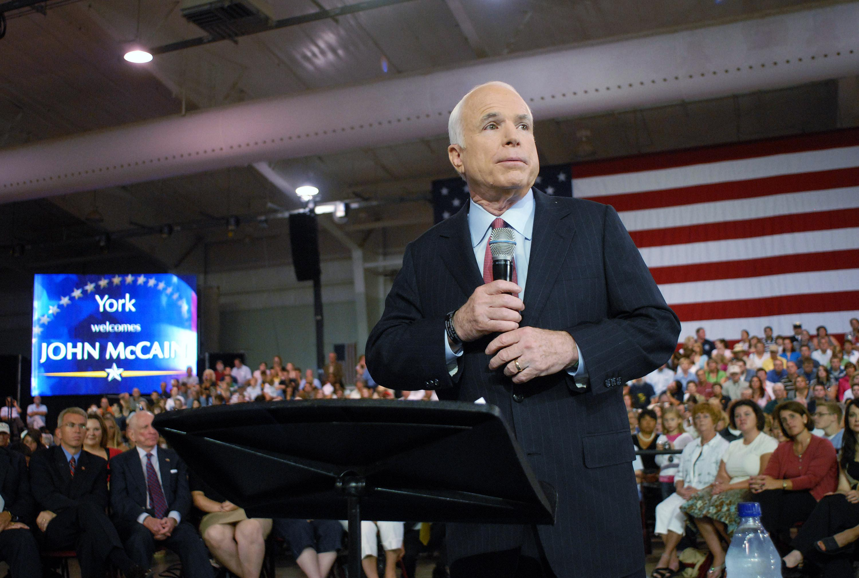 Sen. John McCain at a podium in front of a crowd and an American flag.
