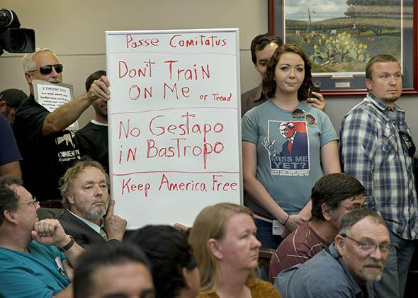Bob Welch (standing at left) and Jim Dillon hold a sign at a public hearing about the Jade Helm 15 military training exercise in Bastrop, Texas, on April 27, 2015.