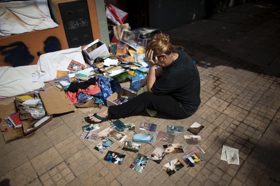 Vilma Gorostiaga cries outside her home as she dries her family pictures on the ground in La Plata, in Argentina's Buenos Aires province on April 4, 2013.