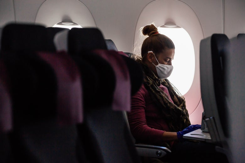 A woman wearing a mask sits on an airplane next to two empty seats.
