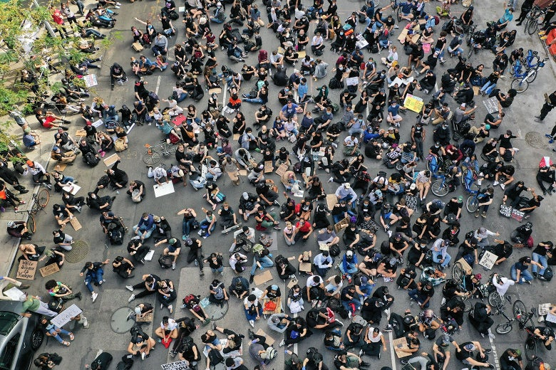 Protesters sit in the road, as seen from above.