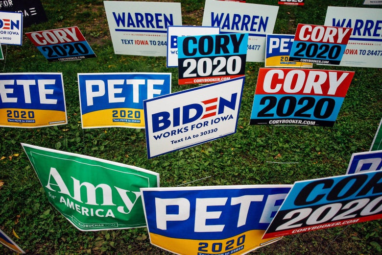 A mass of presidential campaign signs for Amy Klobuchar, Pete Buttigieg, Cory Booker, Joe Biden, and Elizabeth Warren are seen on a field