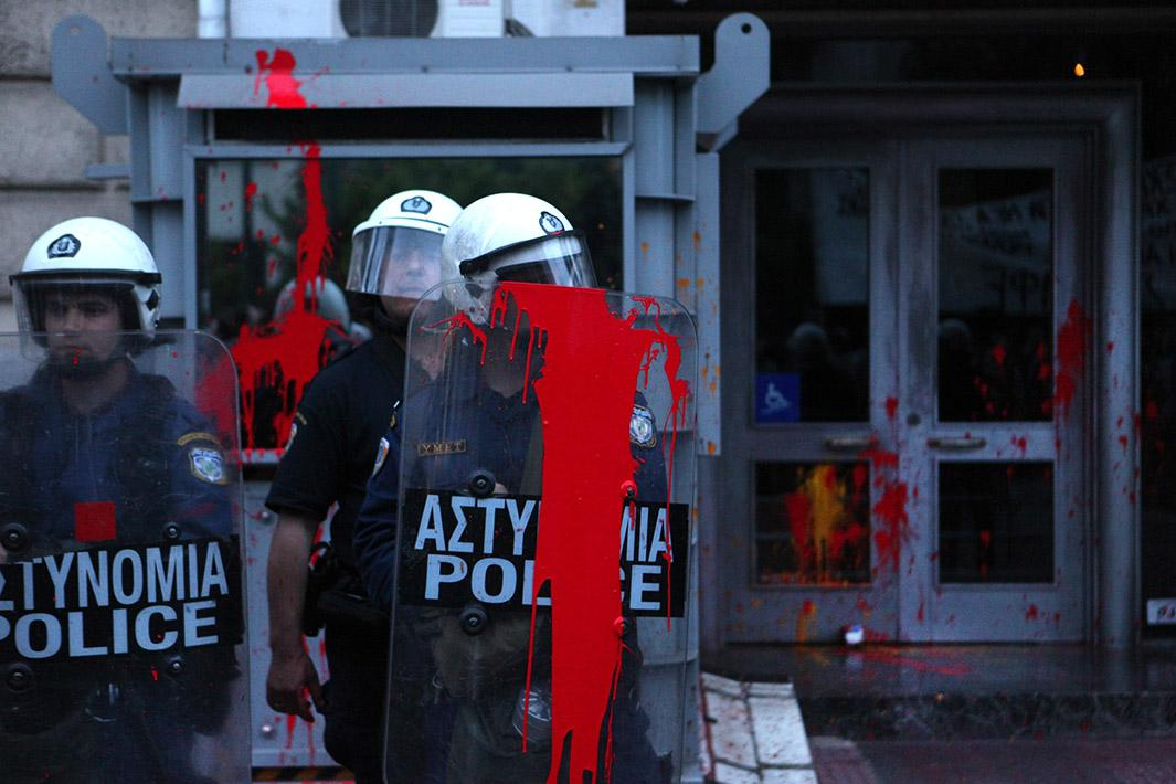 Riot police, hit by red paint ball stand guard as the protesters