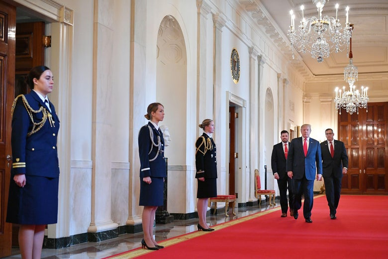 President Donald Trump walks through an ornate hall in the White House.