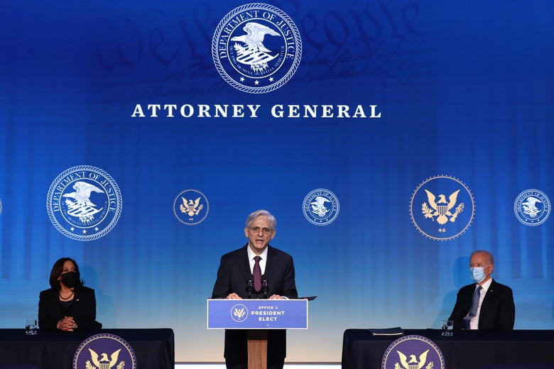 Merrick Garland speaks at a podium labeled Office of the President Elect as Joe Biden and Kamala Harris look on, seated on either side of him on a stage with a backdrop that says Attorney General.