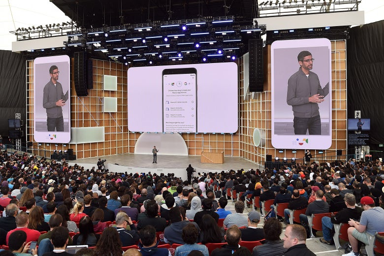 Sundar Pichai stands on a stage, flanked by images of himself on Android phones.