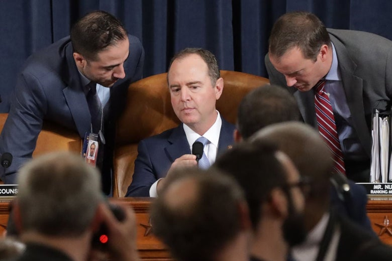 Adam Schiff, seated, listens as two men lean over his shoulders.