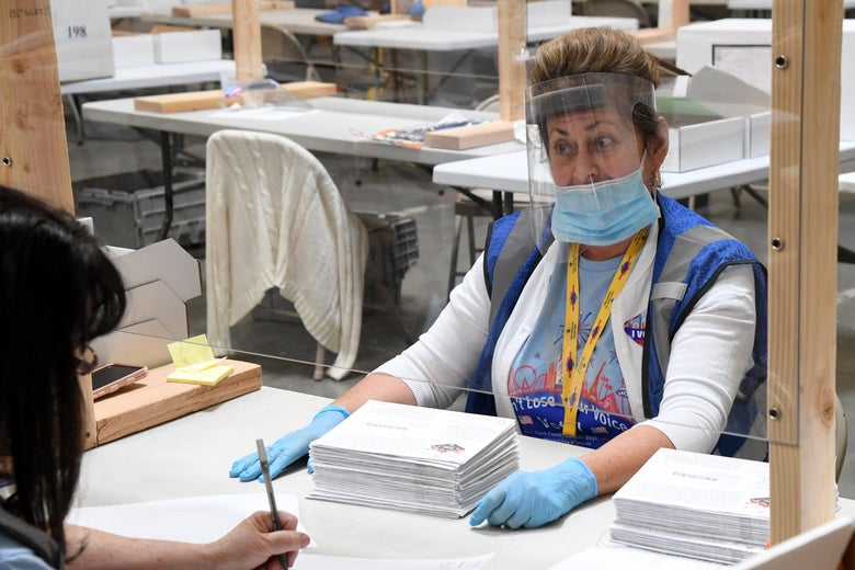 Thompson wears a face shield, mask, and gloves and sits behind a clear screen across from someone filling out a form.