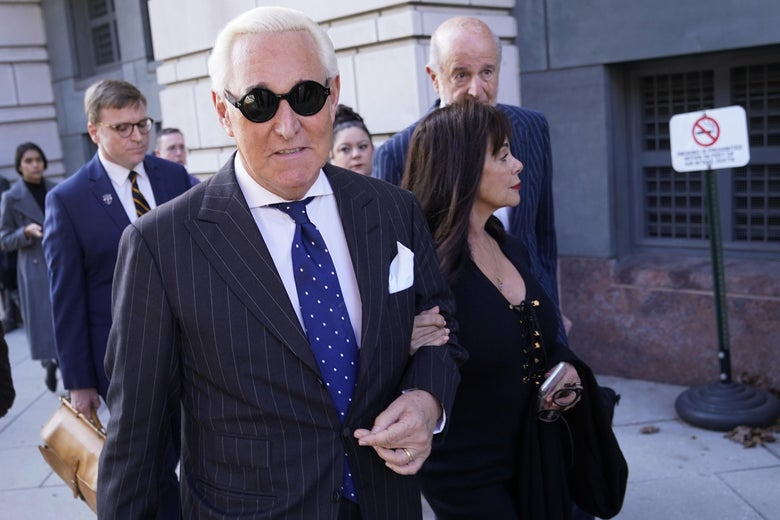 Roger Stone leaves a courthouse wearing some hip sunglasses and accompanied by his wife.
