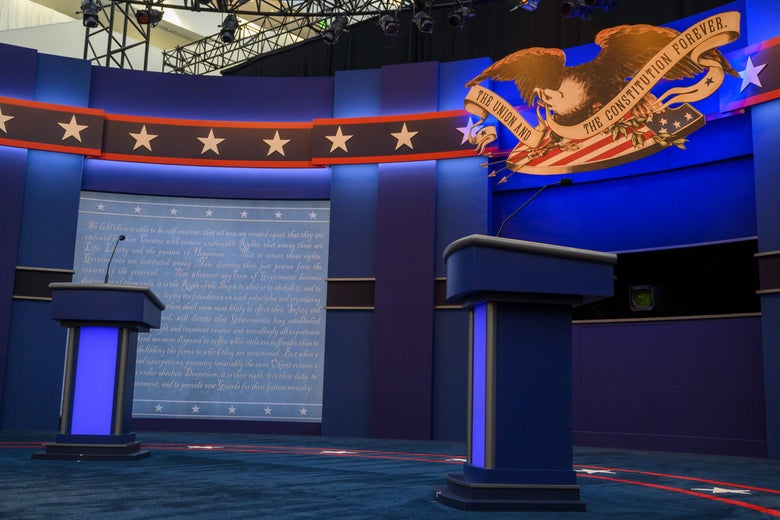 An empty debate stage is seen with lecterns and displays of the Constitution and an eagle.