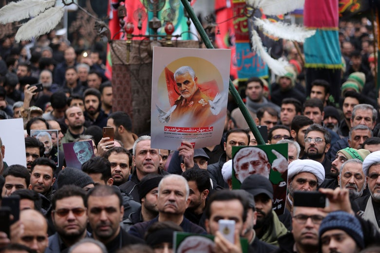 A large crowd of Iranian demonstrators. One holds up a poster of Soleimani.
