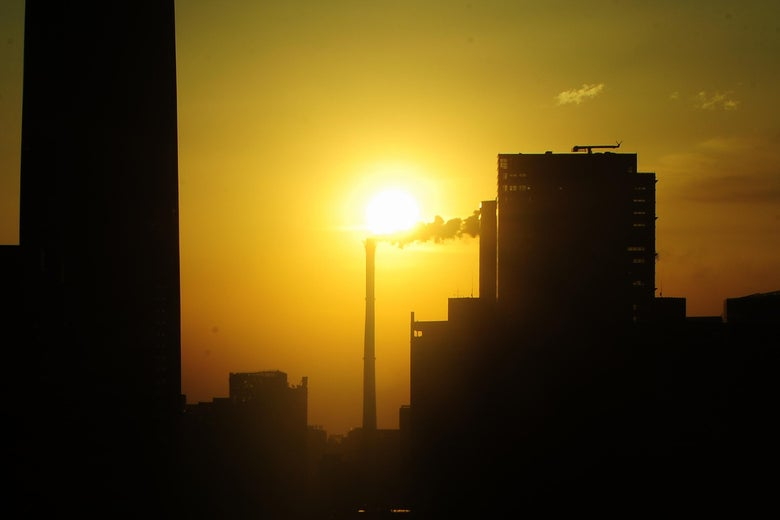 The sun rises in east Beijing behind a smokestack chimney dwarfed by the capital's tallest skyscraper, the China World Trade Tower 3 at the break of day on March 25, 2010.