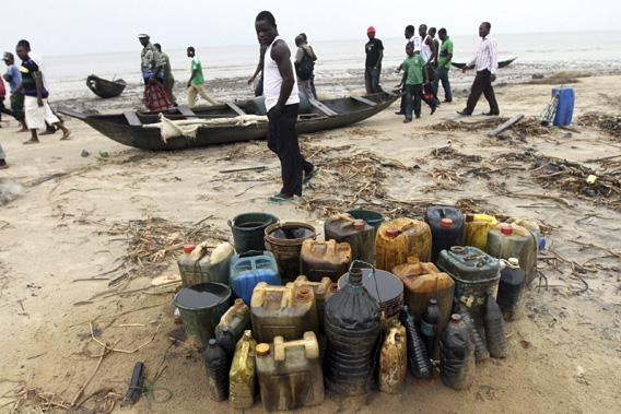 Villagers walk past jerrycans containing crude oil at the shore of the Atlantic ocean near Orobiri village, days after Royal Dutch Shell's Bonga off-shore oil spill in Nigeria's delta.