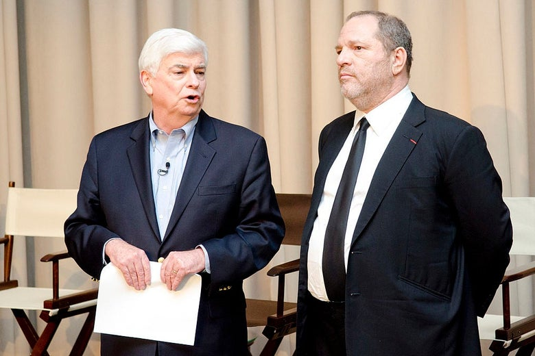 Dodd and Weinstein, wearing suits, stand in front of a row of folding canvas chairs.