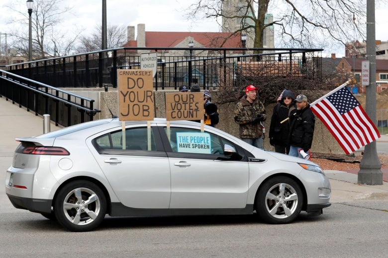 "A car with signs on the window that say ""DO YOUR JOB,"" ""OUR VOTES COUNT,"" and ""THE PEOPLE HAVE SPOKEN"" drives by a group of protesters, one of whom is holding an American flag"
