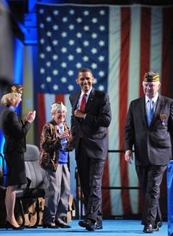 US President Barack Obama walks on to the stage with Veterans of Foreign Wars. Click image to expand.